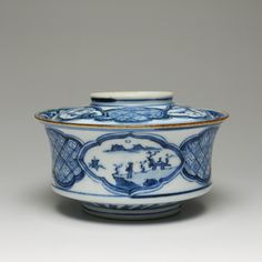 Rice bowl and lid of porcelain, with curving sides decorated in underglaze blue with diamond-shaped cartouches containing landscapes and swastika brocading: Japan, 18th-19th century,