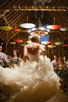 This photo captures the movement of the dress — plus, we love how the colorful parasols brighten up this barn wedding! She's clearly having fun :)