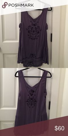 Free People Black & Purple Tunic Top Size small. Criss cross back. Open slit on side. Floral knit pattern in black. High/low. Free People Tops Tunics