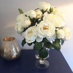 White/Cream Mixed Garden Artificial Roses Arranged In A Glass Vase A stunning arrangement of luxury, artificial white/cream roses displayed in a glass footed vase. Arranged in a glass vase, these beautiful roses appeared to have been picked freshly from your garden this morning. Faux flowers are perfect for brightening up a corner in the sitting room, as a centrepiece on a dining room table, or study window ledge. Approx. size: H: 42cm W: 50cm £124.00