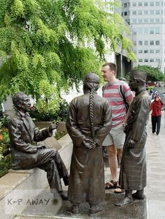 "A tourist enjoying a lively conversation with ""People of the River"" - Singapore River"