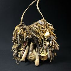 Ceremonial Shell Bilum Bag, Yangoru area of Papua New Guinea This old bilum has the front surface fully covered with various shells, tooth, seeds, sea urchins, and other small objects. These are made like this to not only look beautiful at ceremonies, but to also make a jingling bell like sound when danced. This fine example is classic in nature with a perfect blend of skilfully woven split cane structure and bush string incorporated into the weave. These were also considered a wealth…