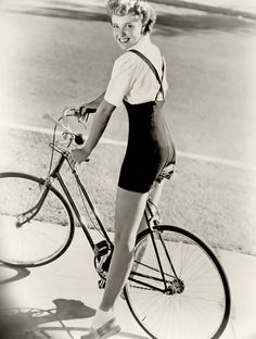 Actress Laraine Day looking cute as a button in her summery shortalls/suspender shorts and blouse as she zips about on a bike. #vintage #1940s #actress #fashion #summer #bicycle