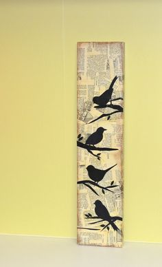 4 bird silhouettes on a newspaper background on a wooden board
