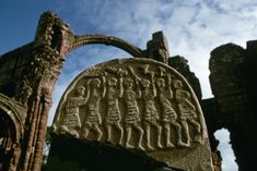 Gravestone depicting Viking marauders, outside the ruins of Lindisfarne Priory, attacked in AD 793. The men shown on this stone grave marker are Viking raiders. The Vikings look fierce and threatening.