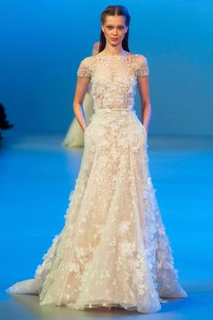 LOVE the floral applique on this Elie Saab short sleeve bridal gown. beaded, flowers, sheer, a line, bridal, wedding dress.
