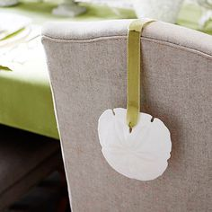 Complete your dining room table with a sand dollar and green ribbon. Simple and beautiful! #CaboChristmas @Better Homes and Gardens
