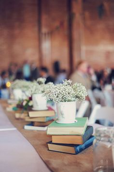 I Love the use of books, coffee mugs, and baby's breath... love this look on the long table!