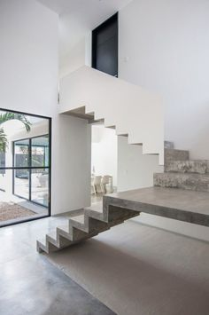 Concrete stairs look like they are floating . I like how the lower flight has no balustrade and the upper flight has a simple white one - Warm Architects