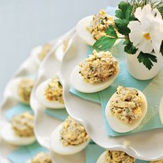 Lemon-Dill Chicken Salad-Stuffed Eggs—Give this Southern favorite fresh flavor by adding dill and shredded chicken. Stacked white cake stands decorated with colored paper napkins create a snappy yet casual centerpiece.| SouthernLiving.com
