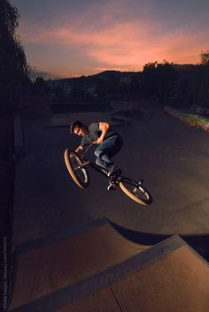 Teenager riding BMX perfoming midair stunts on ramp by RG&B Images for Stocksy United
