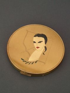 Diane The Huntress Compact   Large guilt metal powder compact with a Diane and Bow design etched to the lid. The lady has painted enamel detail in black and red. It measures 3.75 inches (9.5cm) in diameter. Inside there is a mirror to the lid and a mesh but no puff. Condition is good but there is some hazing to the mirror
