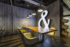 Rustic wood walls & fun light fixtures bring an urban cool edge to this meeting room at EY in Warsaw.