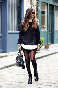 Julie Sarinana of Sincerely Jules wearing a collared button-down shirt underneath a black boxy top, with a black mini skirt, tights, and black Balenciaga ankle boots