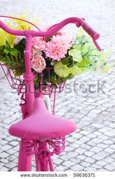 pink painted bicycle with a basket with flowers and leaves