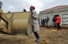 An unidentified woman unsuccessfully tries to prevent workers from demolishing her home in Lenasia, south of Johannesburg, South Africa