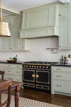 Beautiful kitchen boasts light gray green cabinets paired with black granite countertops and cream glazed tile backsplash. Green Kitchen Cabinets, Kitchen Stove, New Kitchen, Black Cabinets, Kitchen Paint, Kitchen Backsplash, Kitchen Pantries, Backsplash Ideas, Kitchen Laminate