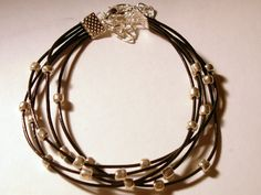 Brown leather bracelet with silver tone beads and clasp.