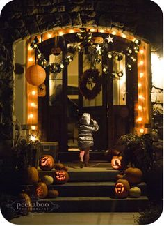 Halloween front porch with lighted arch, glowing Jack-o'-lanterns, dark door wreath, hanging garlands, and Chinese lanterns  | via Peekaboo Photography