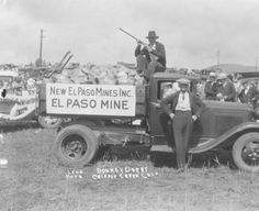 """Cripple Creek, 1920-1930. View of truck from El Paso Mine participating in Donkey Derby, Cripple Creek, Colorado; man with shotgun is seated atop roof of truck which is filled with hardrock ore samples; sign on truck states """"New El Paso Mines Inc.-El Paso Mine"""", crowd of people and automobiles are behind the truck.. Creator: Lehr, Bill. Courtesy: Western History/Genealogy Department, Denver Public Library, Denver, Colorado (USA)."""