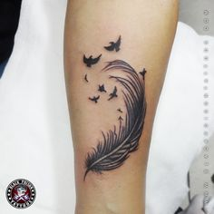 The black feather tattoo above looks cool on the arm and very simple like the type of bird it's derived from.