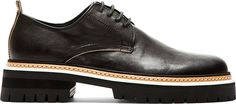 """Low-top leather shoese in black. Round toe. Tonal derby-style lace-up closure. Pull-loop at heel collar. Tan and white layered welt. Stacked foam rubber sole. Approx. 1.5"""" heel."""