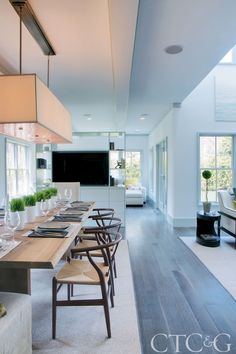 In the dining room, iconic Wegner Wishbone chairs surround a Crate & Barrel table under a rectangular Restoration Hardware fixture. Built-in shelving and an entertainment unit separate the dining and family rooms.