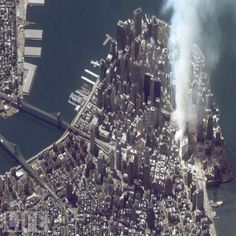 A satellite image of lower Manhattan shows smoke and ash rising from the site of the World Trade Center at 11:43 AM on September 12, 2001. The fires at Ground Zero continued to burn for 99 days after the attack