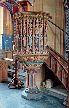 Brightly coloured and richly carved pulpit with polygonal timber shaft and stone base at Long Sutton, Somerset