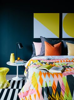 colorful moody bedroom. black and white striped rug + colorful printed bedding. dark walls.