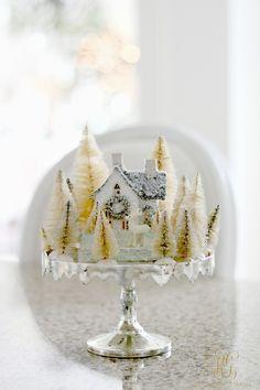 Vintage glitter house with white bottle brush trees vignette on cake stand