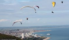 Flying high... while they can: Paragliders take advantage of break in the miserable weather over Beachy Head and Eastbourne in East Sussex today