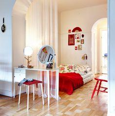 La cama que hay en la zona de descanso y el tocador blanco del salón están separados por un visillo; sin embargo, los asientos, los adornos de la pared y la manta de color rojo los unen de alguna manera.