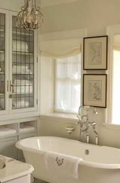 Vintage fixtures and a roll-top pedestal bath tub set the traditional tone of this soothing and elegant principal bathroom. ~built-in cabinets as storage for linens, recycling old leaded windows from elsewhere in the house to create the doors. ~off-white ...