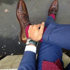 Men's Fashion: It's all about accessories. Raspberry polka dot tie and matching socks are spicing up the blue suit.