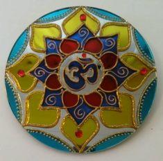 """Mandala em espelho de 15cm de diâmetro, pintura vitral, decorado com tinta relevo dourada e pedrinhas acrílicas. Pode ser feito em outros tamanhos.  Om () é o mantra mais importante do hinduísmo e outras religiões. Diz-se que ele contém o conhecimento dos Vedas e é considerado o corpo sonoro do Absoluto. O Om é o som do universo e a semente que """"fecunda"""" os outros mantras.  O mantra Om é a jóia principal entre os outros mantras. Escutar o mantra Om é como escutar o próprio Brahman, o Ser…"""