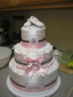 Sophisticated Baby Diaper Cake: I started with a bottle of champagne and surrounded it with three layers of loosely wrapped diapers around the base of the bottle securing the diapers