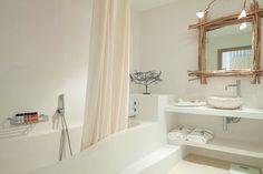 Baños blancos con encanto con bañera de obra y lavabo de piedra. Hotel Mares Formentera