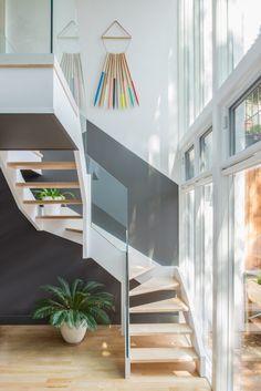 A sala de família, que se abre para a área externa, está confortavelmente mobilada. O cinza escuro envolve a sala, seguindo as escadas.