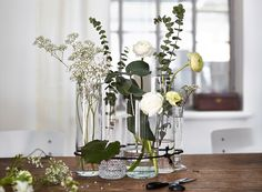 Et romantisk blomsterarrangement med klare vaser bundet sammen med svart hyssing.
