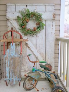Holiday Porch Display of Wooden Door, Wreath, Sled, and Well-Used Vintage Tricycle