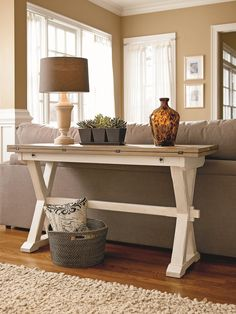 Aparador simples em branco com pés em x decorado com abajur ter colocado nas costas do sofá.