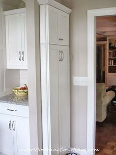 Narrow kitchen cabinet command center added to end of a bank of cabinets broom and mop storage