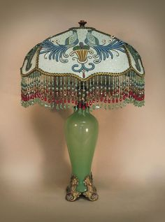 $4,070.00   'DROOP' shaped shade sets upon a glorious, green, translucent glass table lamp with bronze dore base, each corner of which is an Egyptian themed lady's head. The shade is light green, covered with pale green silk flecked with tiny silver dots then overlaid with hand embroidered bird and flower basket appliqués. Glorious, hand beaded fringe with red accents.