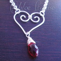 "Chloe @ chloelouisejewelry.etsy.com  ""Hammered Heart Necklace""  Handmade silver filled wire heart necklace with and beautiful red Czech crystal tear drop hanging below.   The chain is silver tone 18"" long.   Closes with a lobster clasp."