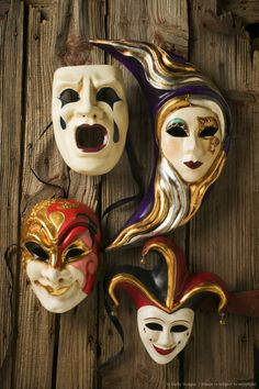 Masquerade masks and theater mask hanging on wooden wall