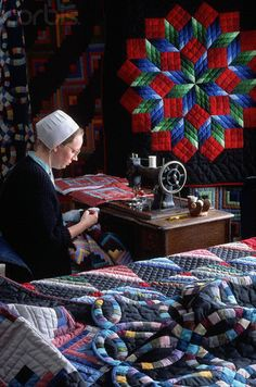 Amish woman piecing a top, using a treadle machine [Great Rolling Star on the wall above her machine, and nice Wedding Ring and Amish Shadows displayed on the bed.