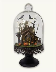 Trapped within the eerie glow of a glass bell jar, a foreboding haunted house in a spooky graveyard is besieged by bats from the belfry and ghosts in the attic.