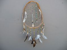 This Dream Catcher has a curved frame made of Wisteria Vines, surrounded by a series of Chicken, Duck, and Rooster Feathers. The Dream Catcher itself has 2 Antiqued Buffalo Teeth at the bottom of the