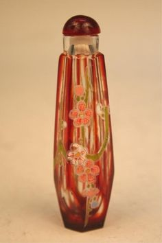 Small, red corked perfume bottle with floral  enamel decoration, glass; unsigned.  Dimensions: 3-5/8H x 3/4 diameter